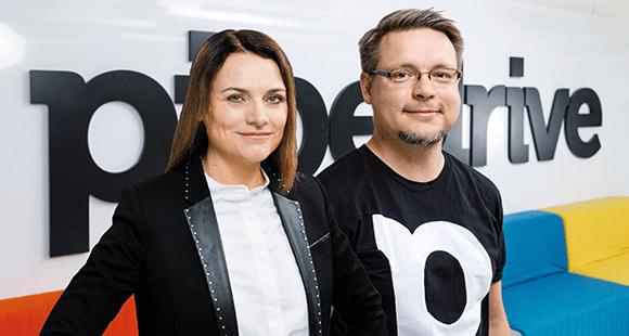 Laurence Bret-Stern und Martin Henk stehen vor einer Wand mit dem Pipedrive-Logo
