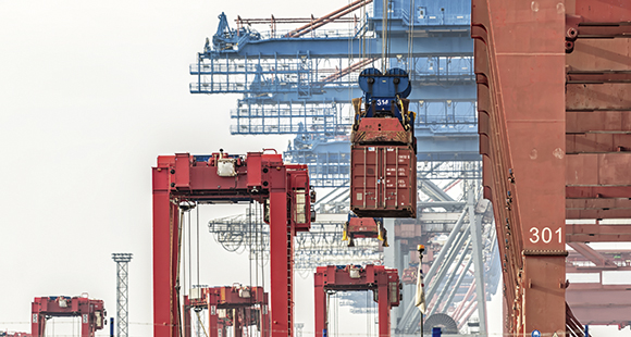 Hochbetrieb im Hafen: Container werden vom Schiff auf Portalhubwagen verladen und zum vorläufigen Lagerplatz gebracht